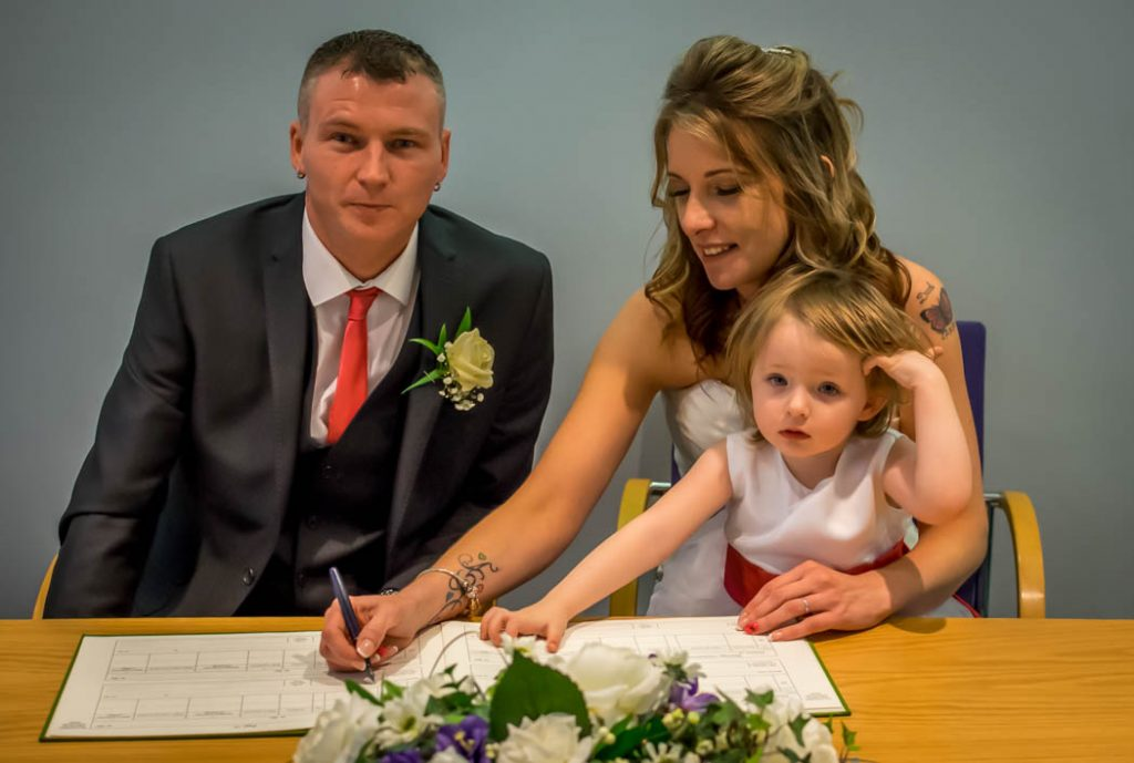 signing of the registerbride and groom in Wedding photography East Dereham Registry Office Norfolk