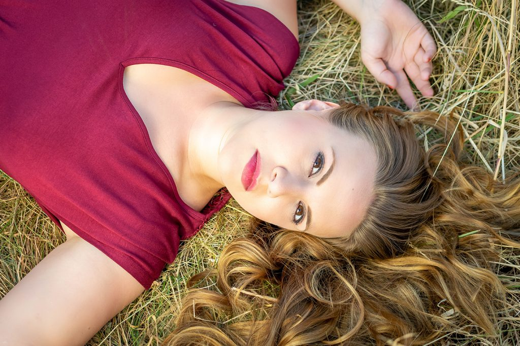 Red dress in the dry meadow fashion portraits